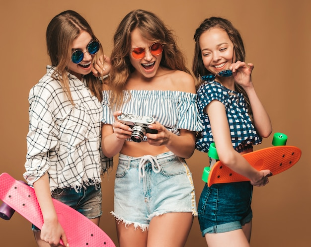 Three beautiful stylish smiling girls with colorful penny skateboards. women in summer checkered shirt clothes. taking pictures on retro photo camera