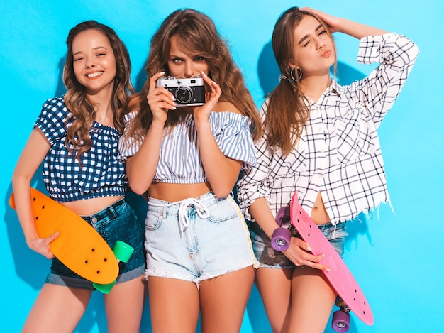 Three beautiful stylish smiling girls with colorful penny skateboards. women in summer. taking pictures on retro photo camera