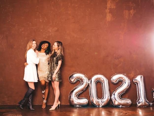 新年を祝う3人の美しい女性。スタイリッシュで幸せなゴージャスな女性
