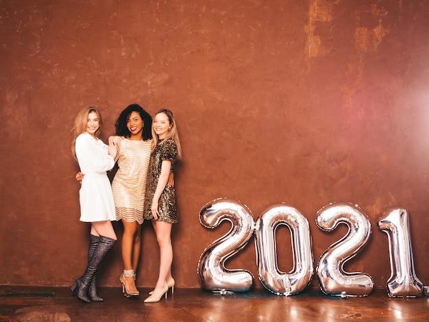 Tre belle donne che celebrano il nuovo anno. felice splendida femmina in stile