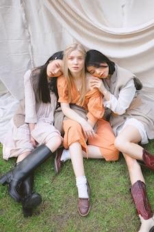 Tre belle donne che si siedono sulla terra e che guardano nel giardino.