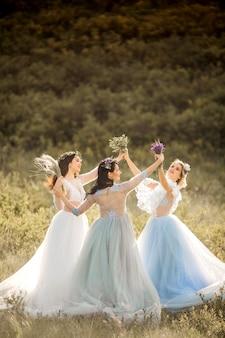 エレガントなドレスと花輪を持つ3人の美しい女性