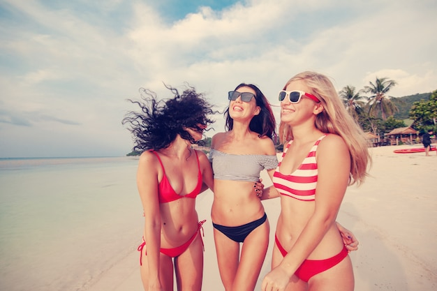 Three beautiful young european slender girlfriends in bright red and striped bikinis walk on a tropical beach on vacation, happiness joy summer and fun