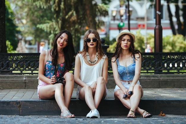 공원에 대항하여 포즈를 취하는 세 명의 아름다운 어린 소녀들