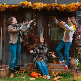Three beautiful young women, cheerfully throwing a yellow autumn leaf, smiling on an old wooden background. the autumn fashion season.