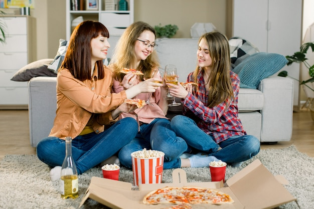 Three beautiful young women drinking wine and eating pizza at home. happy beautiful friends laughing, eating pizza at home party. woman having dinner together, enjoying meal. leisure, friendship