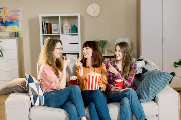 Three beautiful young women friends at home eating popcorn sitting on gray sofa together and laughing. home women party