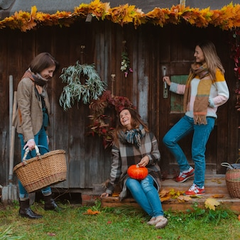 Three beautiful young women, having fun with a yellow autumn leaf, smiling on an old wooden background. the autumn fashion season.