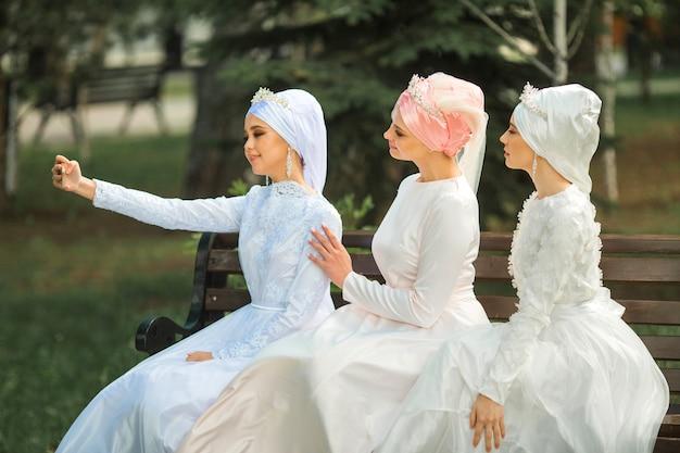 Три красивые молодые женщины в праздничных мусульманских платьях делают селфи по телефону