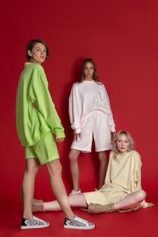 赤い背景にポーズをとって月色のスポーツウェアの3人の美しい若い女性