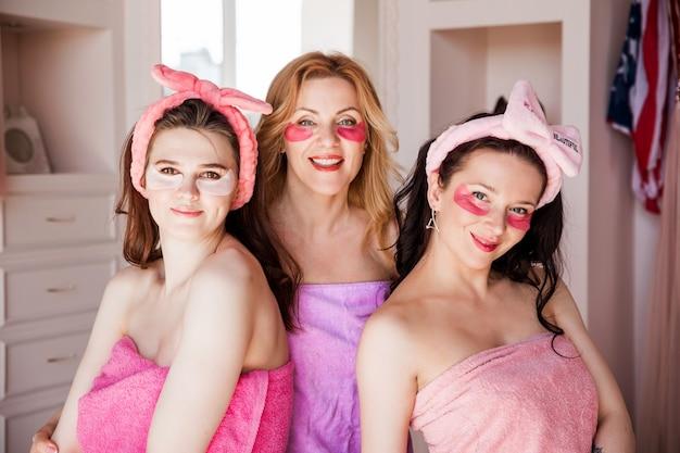 Три красивые молодые женщины в розовых полотенцах, с косметическими повязками на голове, позируют перед камерой с пятнами под глазами. .