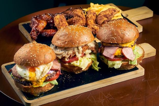 Три гамбургера из говядины с сыром, яйцом и салатом на черной доске. быстрое питание
