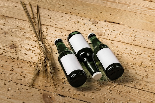 Three beer bottles and ears of wheat on wooden background