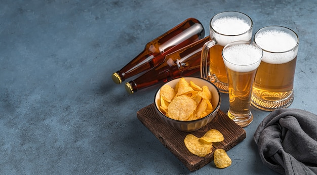 Three beer mugs chips and beer bottles on a dark blue background Premium Photo