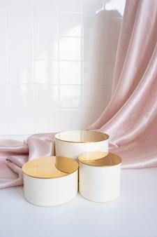 折り目が付いたサテンの背景にゴールドのトップが付いた3つのベージュの表彰台トッパー。浴室の背景タイル。