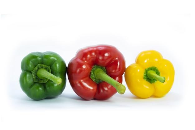 3つのベルペッパーは白地に赤、緑、黄色です。カラフルな野菜。