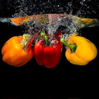Three bell peppers falling into the splash water