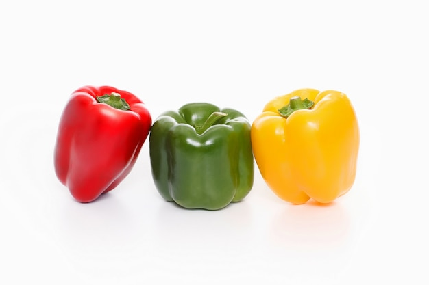 Three bell peppers, red, green and yellow on white background,