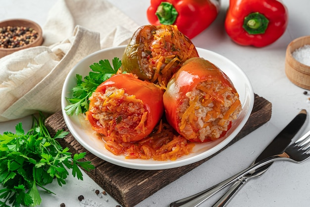 Three bell peppers stuffed with turkey and rice on a light gray background