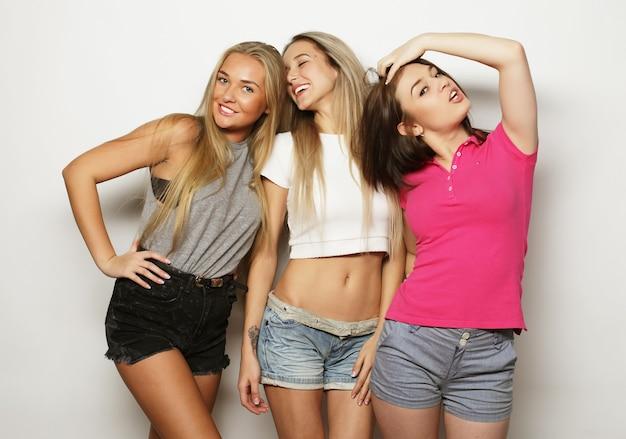 夏のスタイルの衣装とジーンズのショートパンツを着て、スタジオでポーズをとる3人の親友。笑顔で楽しんでいる女の子。