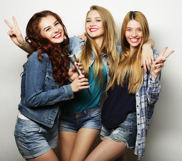 Трое лучших друзей позируют в студии в летней одежде и джинсовых шортах. девушки улыбаются и веселятся.