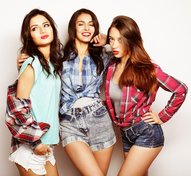 Three best friends posing in studio, wearing summer style outfit and jeans shorts