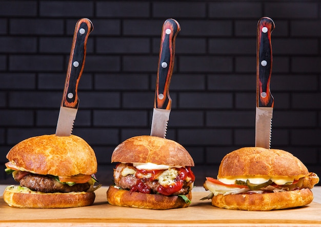 Three big burgers on wooden table on black bricks background in the restaurant. fast food