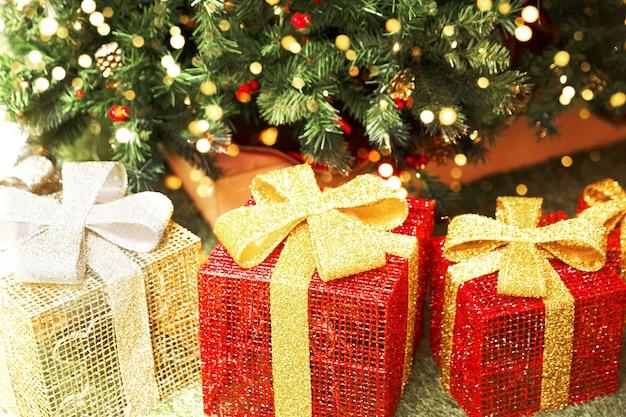 Три большие блестящие подарочные коробки под елкой. праздничная концепция.