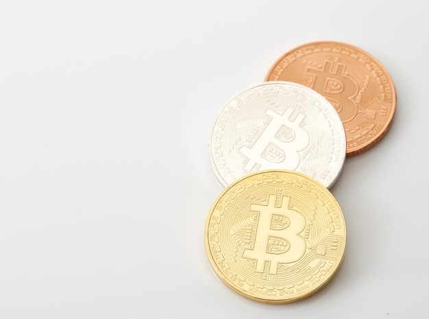 Three bitcoins coins on white