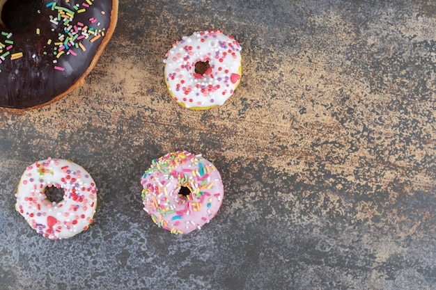 나무 표면에 큰 도넛 한 개 옆에 한 입 크기의 도넛 세 개
