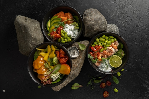 Three black ceramic bowls with assorted vegetarian asian dishes of fish, shrimp, seafood, beans and avocado with yogurt dressing.