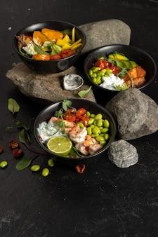Три черные керамические миски с ассорти вегетарианских азиатских блюд из рыбы, креветок, морепродуктов, бобов и авокадо с йогуртовой заправкой.