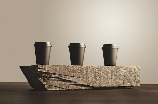 Three black take away paper cups with closed caps isolated on wooden brick on table