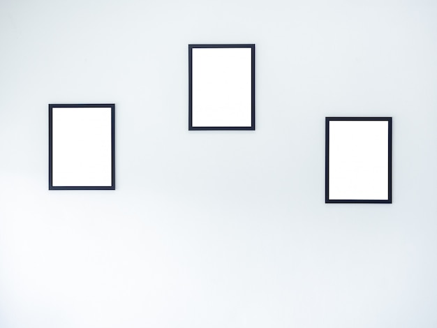 Three blank frames on white wall background