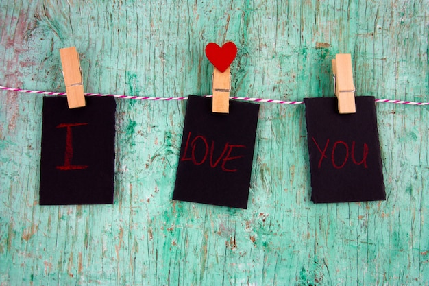 Three blank  labels with inscription i love you and paper red heart on cloth pins hanging on a rope