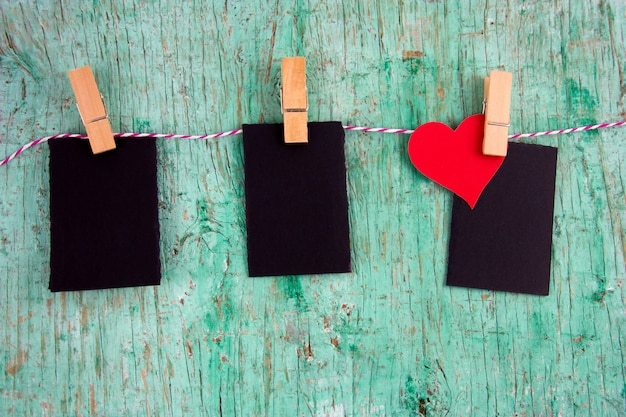 Three blank mock up labels and paper red heart on cloth pins hanging on a rope