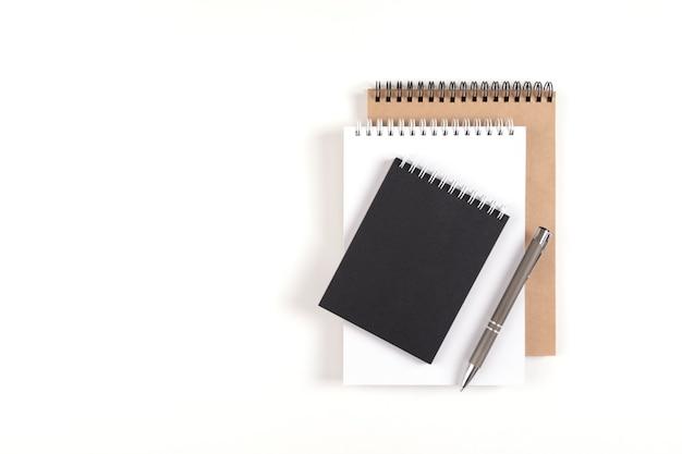 나선형에 세 개의 빈 메모장이 흰색 배경에 스택에 쌓여 있습니다. 흰색, 검은색 및 재활용 시트와 펜이 있는 노트북. 교육, 사무실입니다.