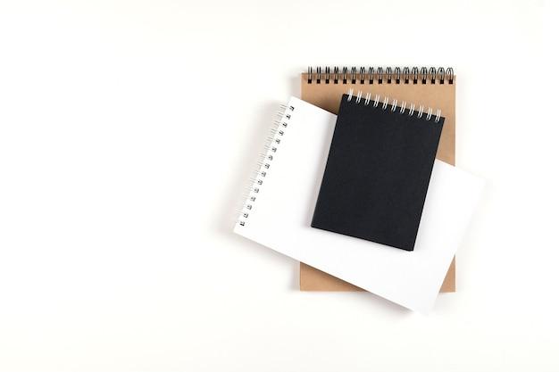 나선형에 세 개의 빈 메모장이 흰색 배경에 스택에 쌓여 있습니다. 흰색, 검은색 및 재활용 시트가 있는 노트북. 교육, 사무실입니다.