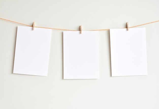 Three blank white papers hanging on the wall, mock up