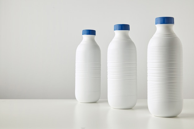 Three blank white plastic riffled bottles with blue caps in row isolated on table