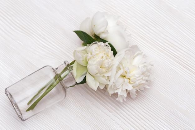 ガラス花瓶に咲く3つの牡丹の花。テーブルの上に花瓶が落ちました。上面図。ソフト選択的フォーカス。