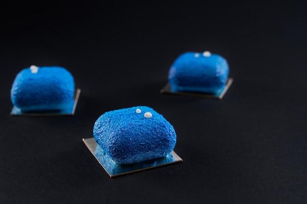 黒で隔離されたマットな表面を持つ3つの青いケーキ。