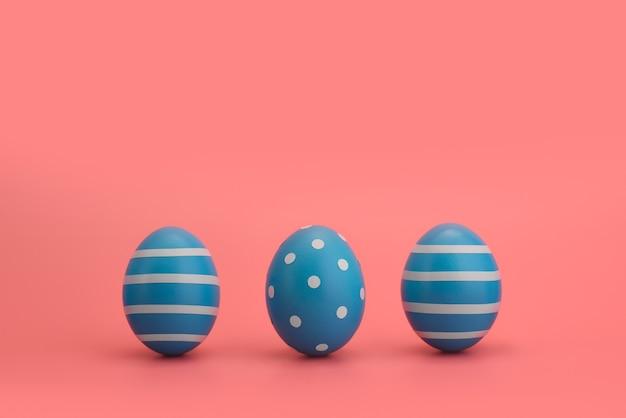 白い縞模様と円で一列に並んだ3つの青い装飾された卵。コピースペース