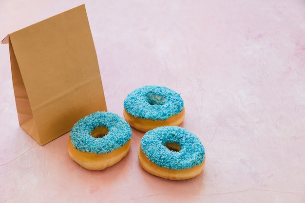 Three blue donuts with parcel on pink background