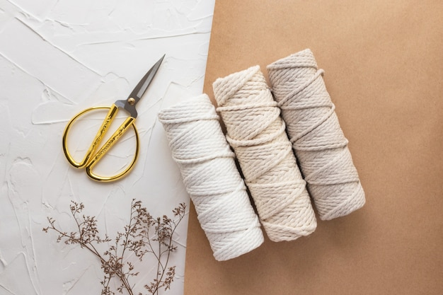 Three bobbins of cotton rope for macrame, handmade in pastel natural colors, scissors for needlework, dry herb, craft paper. white background, top view, flay lay.