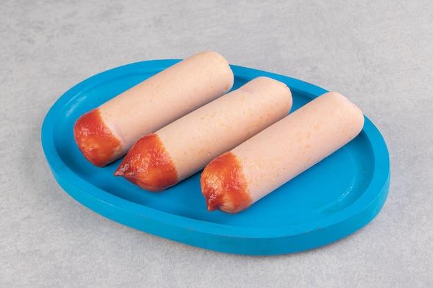 Три вареные колбаски с кетчупом на синей тарелке.