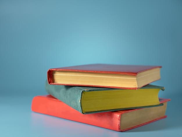 Three books on a blue wall