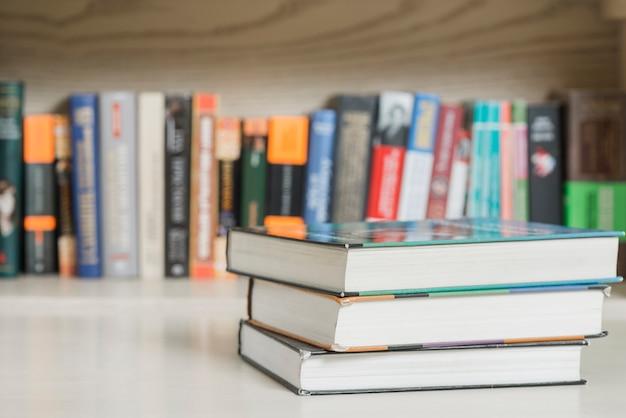 Три книги возле книжной полки