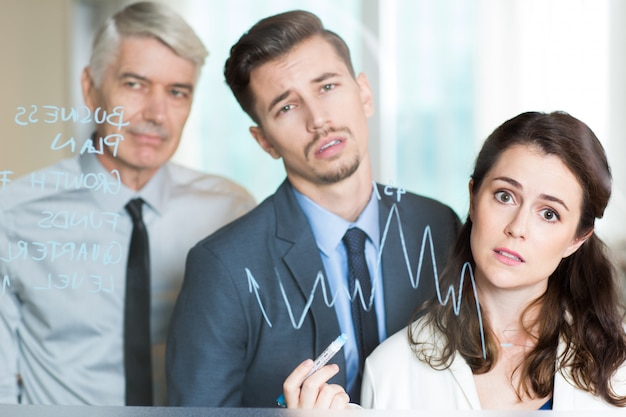 Three bored business people analyzing graph
