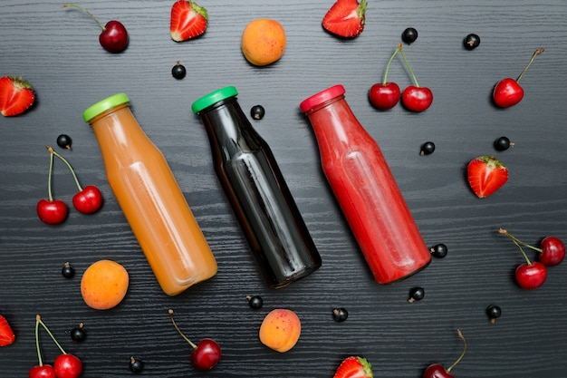 Three bottles of juice and fruits. black wooden . food